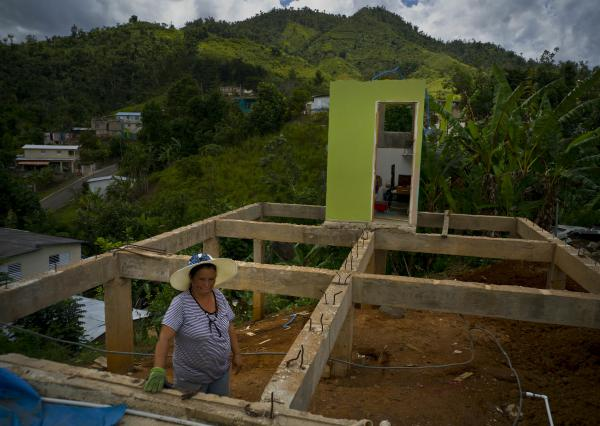 Alma Morales Rosario stands between the beams of her home, in the San Lorenzo neighborhood of Morovis, Puerto Rico, which was being rebuilt in September 2018 after being destroyed by Hurricane Maria.