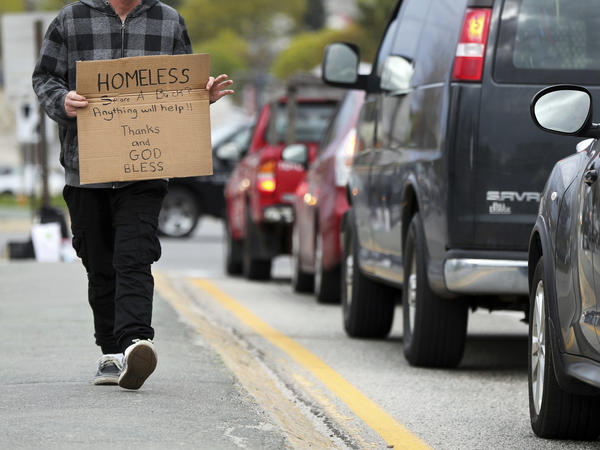 A man panhandles in the median strip on a street in Portland, Maine, in 2017. A federal judge in Arkansas ruled Tuesday that a law forbidding panhandlers to physically interact with people in cars is unconstitutional.