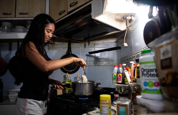 A woman cooks lunch in her house in Manila.