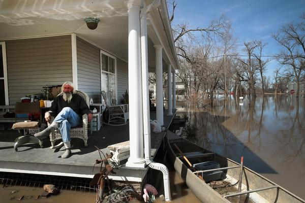 Mike Rasnic sits on the front porch of his home which is surrounded by floodwater on March 22, in Craig, Missouri. Midwest states are battling some of the worst flooding they have experienced in decades.