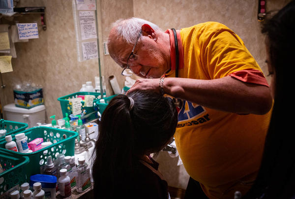 Dr. Carlos Gutierrez examines a young girl at a shelter in El Paso that was set up for recent migrants. The girl's mother said her daughter's deep cough arose while the family was in immigration custody.