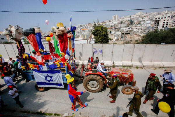 Israeli settlers celebrate the Jewish Purim holiday on al-Shuhada Street in the divided West Bank town of Hebron on March 21.