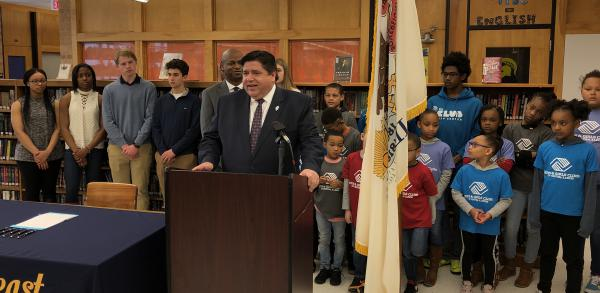 Gov. J.B. Pritzker speaks with reporters before signing legislation at Southeast High School in Springfield, Illinois.