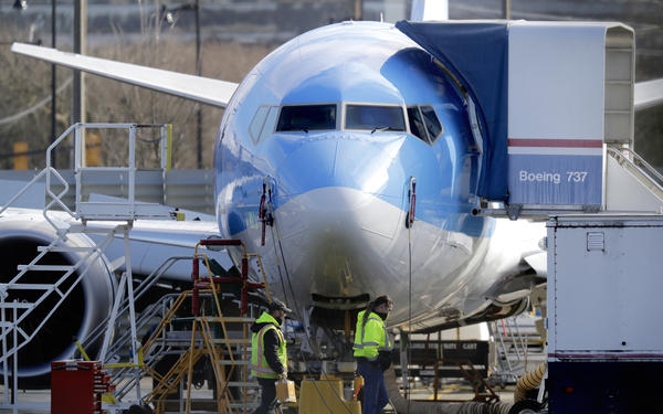 Workers walk past a Boeing 737 MAX 8 airplane being built for TUI Group at Boeing Co.'s Renton Assembly Plant Wednesday, March 13, 2019, in Renton, Wash.