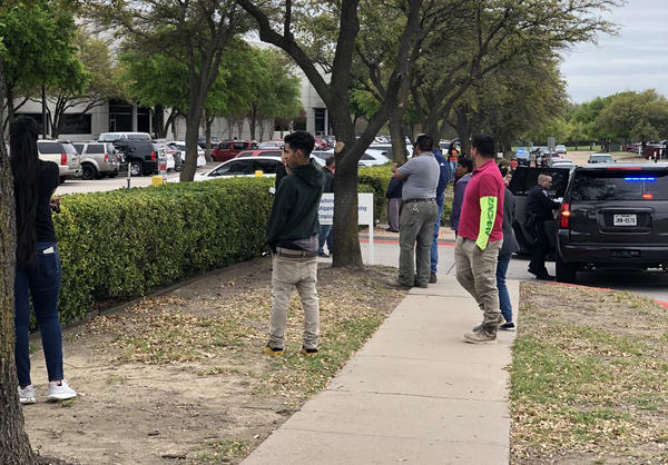 Family of employees inside CVE Technology Group in Allen, Texas, gather outside the building, where the ICE operation is taking place.