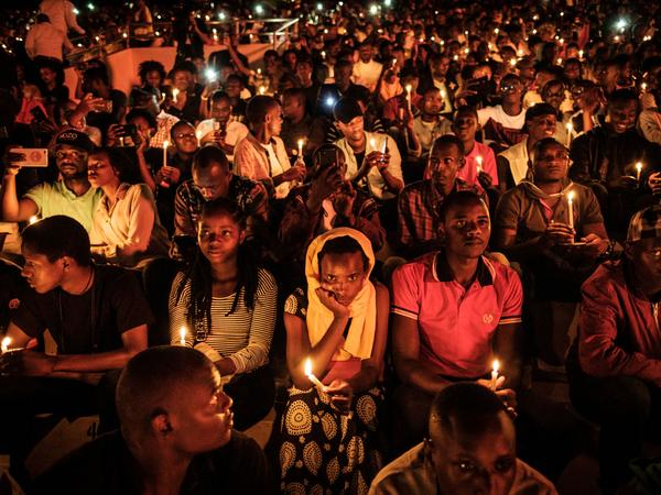 People hold candles during a night vigil and prayer to mark the 25th anniversary of the 1994 genocide, in Kigali, Rwanda, on Sunday. Rwandans began 100 days of mourning for more than 800,000 people killed.