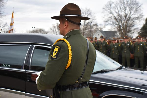 An Illinois state trooper prepares to approach the family of Trooper Brooke Jones-Story after her funeral ended in Warren, Ill.