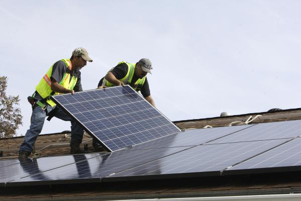 Workers install a rooftop solar panel on a home.