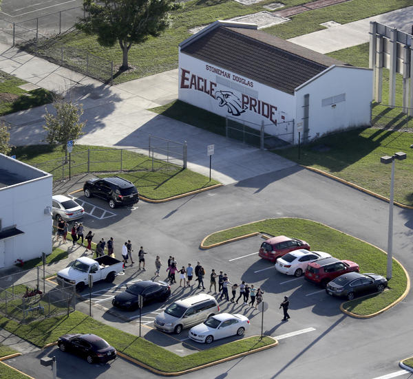 Authorities evacuate students and staff inside the Marjory Stoneman Douglas High School after the shooting of Feb. 14, 2018.