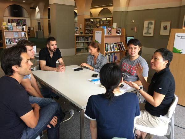 Min Shaheen (right) leads her weekly English conversation circle at the library. About seven participants discuss current events at the Miami-Dade Library's main branch in downtown Miami.