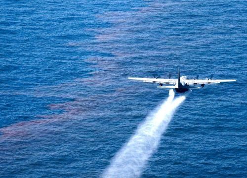 A plane drops chemical dispersant onto a sheen of oil during the BP oil spill.