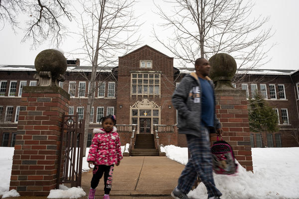 A child and an adult leave Farragut Elementary School in St. Louis' Greater Ville neighborhood in January.