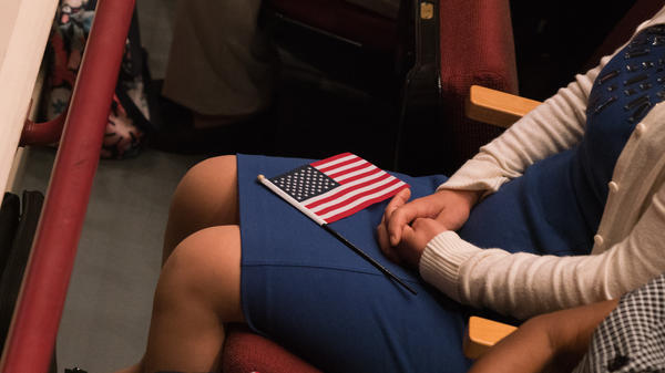 A U.S. flag sits on the lap of a newly sworn-in citizen at a 2018 naturalization ceremony in Alexandria, Va. A new appeal in one of the lawsuits over the addition of a citizenship question to the 2020 census could complicate final preparations for the head count.