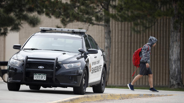 A student leaves Columbine High School late Tuesday in Littleton, Colo. The school was closed Wednesday while authorities looked for a woman they said presented a credible threat ahead of the 20th anniversary of the mass shooting there.
