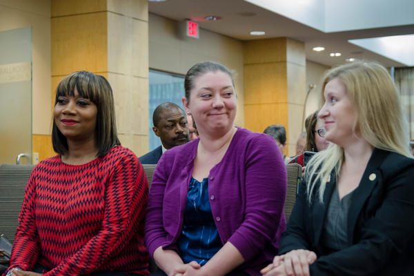 St. Louis Board of Education President Dorothy Rohde-Collins, center, smiles at school board member Natalie Vowell following a vote to reinstitute the board's control of St. Louis Public Schools. Board member Susan Jones is at left.