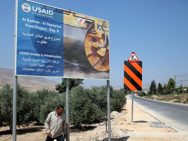 A Palestinian man walks near a USAID billboard in the West Bank village of Badhan, north of Nablus, last August. Since January, U.S. financing for humanitarian programs serving Palestinians has been suspended