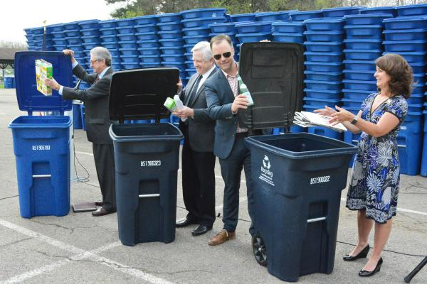 Community representatives ceremonially toss recycleales into bins that will be distributed to their residents.