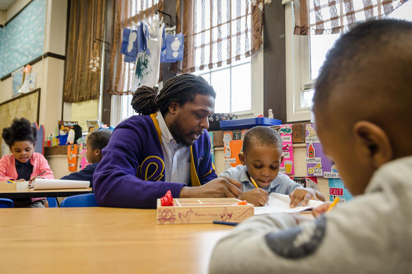 Meramec Elementary School Principal Jonathan Strong works with a preschool student on writing letters. Strong will have more flexibility next year to improve the St. Louis school.