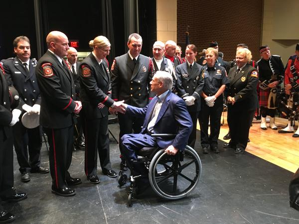 Gov. Greg Abbott shakes hands with volunteer firefighters at the unveiling of the West fertilizer plant explosion memorial.