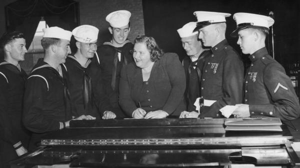 Singer Kate Smith signs autographs for a group of American sailors circa 1938.