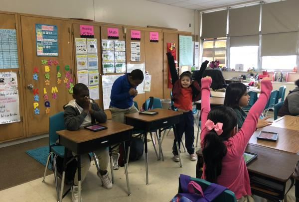 Students in Michelle Olivarri's third grade class celebrate getting the right answer on a computer game.