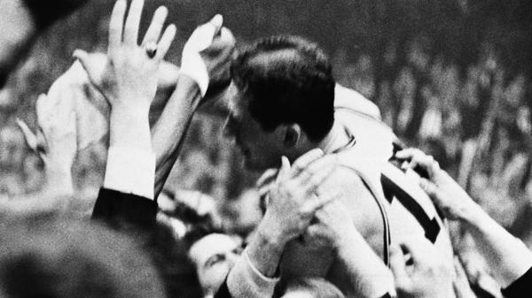 John Havlicek is mobbed by fans after the Celtics defeated the Philadelphia 76ers to win Game 7 of the 1965 Eastern Conference final. Havlicek intercepted a Philadelphia inbound pass in the last seconds of the game.