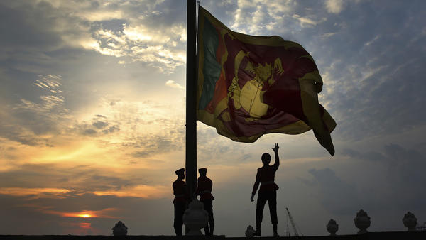 Sri Lankan soldiers lower the national flag in Colombo on Sunday. President Maithripala Sirisena banned face coverings under an emergency law that went into effect Monday.