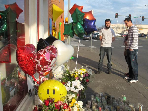 Pedestrians view a memorial in Pasco, Wash., on the sidewalk where Antonio Zambrano-Montes, an unarmed man who was fatally shot by police.