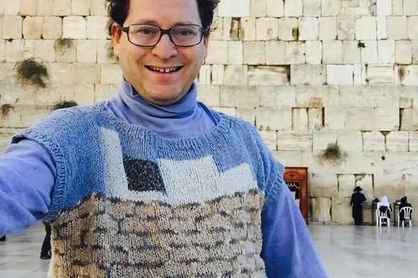 The knitter flashes a smile at Jerusalem's Western Wall.