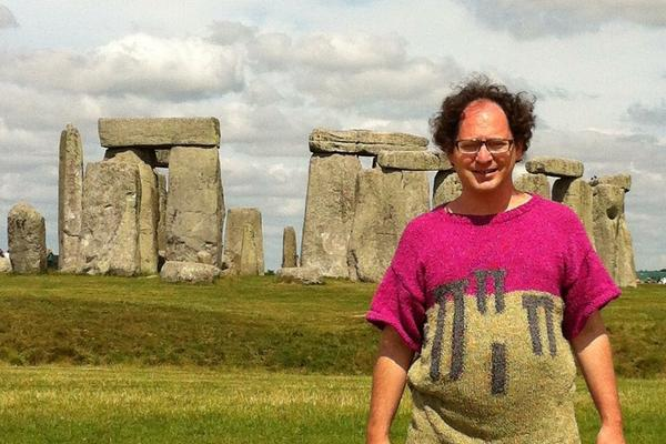 Wearing the appropriate attire, knitter Sam Barsky stands in front of Stonehenge.