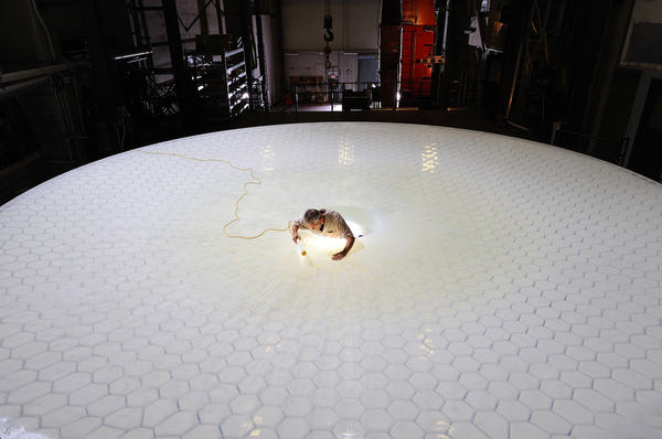 A technician examines the mirror on the Large Synoptic Survey Telescope. Scientists at two national laboratories are currently building the components for an enormous digital camera that will capture images from the telescope.