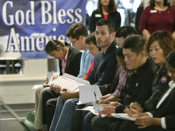 Newly naturalized U.S citizens complete voter registration forms in Bethel Park, Pa., in November 2017. The 2020 census will ask respondents whether they are citizens.