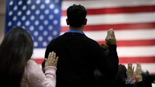 People take the oath of allegiance to become U.S. citizens during a naturalization ceremony at the Los Angeles Convention Center in 2017.