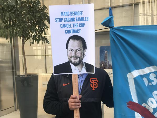 A protester holds up a sign targeting Salesforce CEO Marc Benioff outside the company's headquarters in San Francisco on Monday.