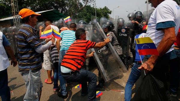 Supporters of Venezuela's opposition leader Juan Guaido struggle with members of Venezuela national police at the Francisco de Paula Santander International Bridge between Cúcuta in Colombia and Ureña in Venezuela, on Saturday.
