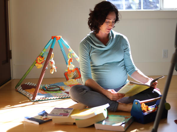 Lesley McClurg sits on the floor of her home in Oakland, Calif., reading a birthing book. McClurg has been taking the time to decide between having a home birth or a hospital birth.
