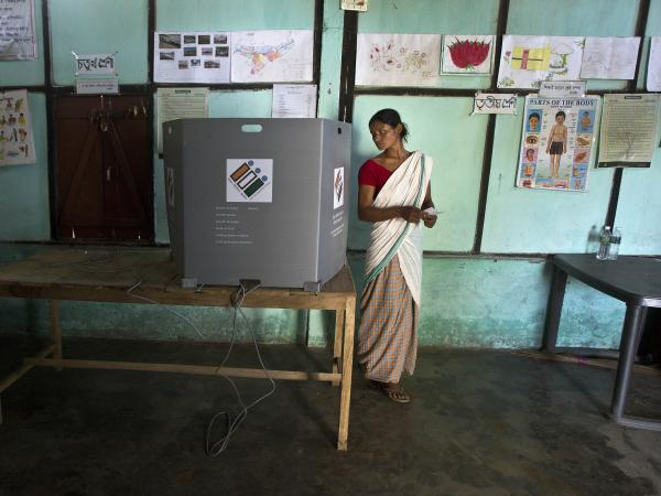 An Indian Mishing tribal woman looks back to ensure her vote has been cast as she prepares to leave the voting compartment during the first phase of general elections in Majuli, Assam, India, Thursday.