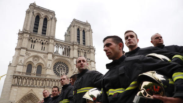 Firefighters line up as they wait for French Interior Minister Christophe Castaner outside Notre Dame cathedral in Paris on Tuesday.