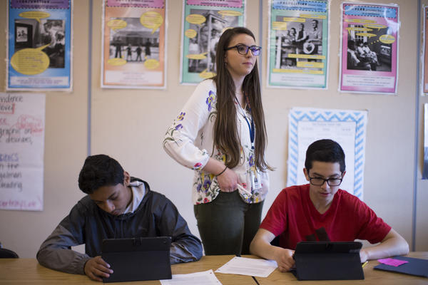 Victoria Libsack, a teacher at Linus Pauling Middle School in Corvallis, Ore., with students Alan Gallardo, 14, (right) and Victor Hernandez, 14. Libsack taught for three years in a low-income Phoenix school. But after her TEACH Grants were converted into more than $20,000 in loans, she took a job at a school that doesn't meet TEACH requirements.