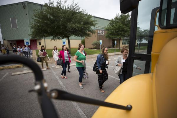 A group of real estate agents boards a school bus for a six-hour tour of Austin ISD schools.
