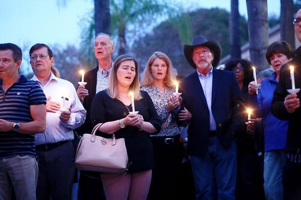 Mourners, including Poway Mayor Steve Vaus (hat) and his wife Corrie, participate in a candle light vigil for the victims of the Chabad of Poway Synagogue shooting at the Rancho Bernardo Community Presbyterian Church on April 27, 2019 in Poway, California.