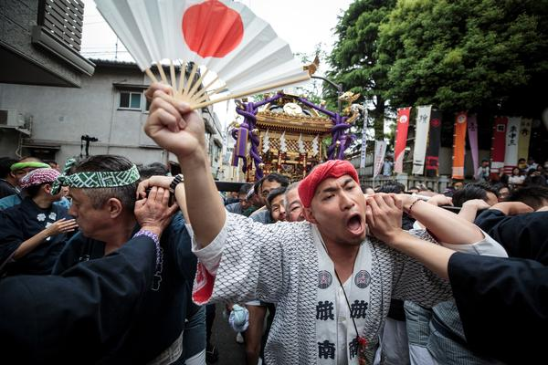 People carry a portable shrine during a ceremony to celebrate the accession of the new emperor to the throne in the Nakanobu neighborhood of Tokyo on May 1, 2019.