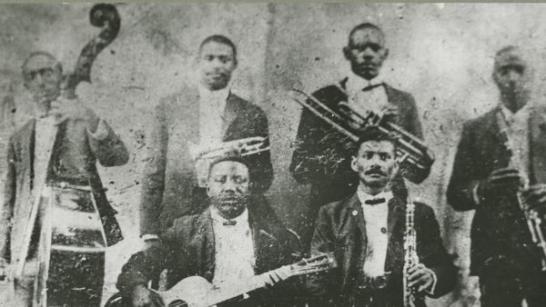 The only known photograph of Buddy Bolden, standing back row and second from left, horn in hand. Also pictured: guitarist Brock Mumford, bassist Jimmie Johnson, clarinetists Willie Warner and Frank Lewis, and trombonist Willie Cornish.