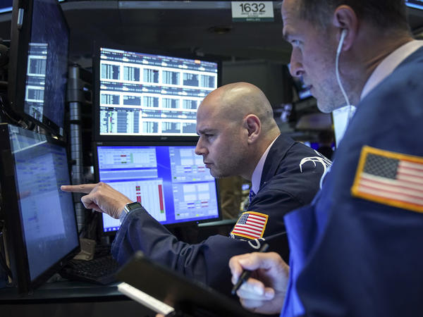 Traders and financial professionals work on the floor of the New York Stock Exchange on Monday. U.S. stock markets fell sharply at the open but crept higher as the day wore on after President Trump threatened to raise tariffs on imports from China.