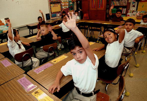 Monolingual Hispanic students raise their hands to answer a question during a class taught in Spanish at Birdwell Elementary School in Tyler, Texas.