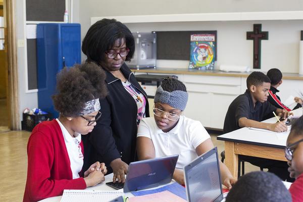 River Roads Lutheran School Principal Yvonne Boyd works with students Sadie Turner and Amyah Gilbert.