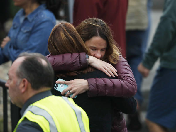 Parents hug as they wait to be reunited with their children after a shooting at a suburban Denver school.