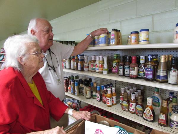At the Bread for Life Community Food Pantry in Bardstown, Kentucky volunteer Don Bresnahan assists 84-year-old client Mildred Beavers.