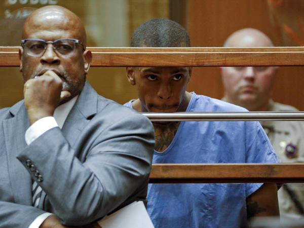 Christopher Darden, (left), is seen in Los Angeles County Superior Court with his now former client Eric Holder. Holder is accused of killing rapper Nipsey Hussle in March.