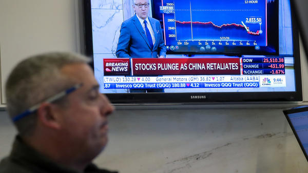 U.S. stocks fell sharply Monday after China retaliated for President Trump's latest round of tariffs. Here, a trader works on the floor at the New York Stock Exchange as a TV shows the state of the market.